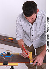 Closeup of a man marking a straight line on a piece of wooden flooring