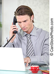 Young businessman on the phone while using his laptop