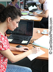 Woman in a busy office working at a laptop