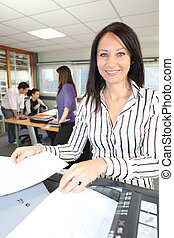 Smiling woman using a photocopier