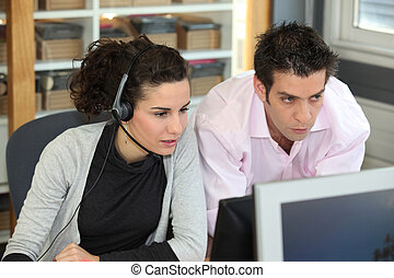 two office colleagues looking at a screen