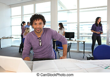 young man in architect's office with laptop and plans