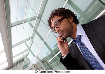 Businessman outside office making phone cal