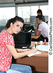 Woman glancing up from her desk in a busy office