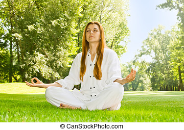 Young woman practicing yoga meditation in the park