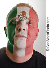 Face of serious patriot man painted in colors of mexico flag...