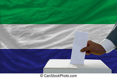man putting ballot in a box during elections in front of...