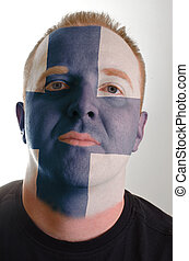 Face of serious patriot man painted in colors of finland...