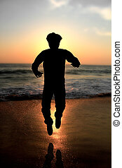 young male adult jumping at evening on a beach - Silhouette...