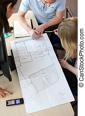 People looking at the layout of a house