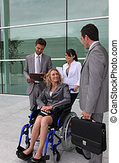 Businesswoman in a wheelchair with colleagues outside an...