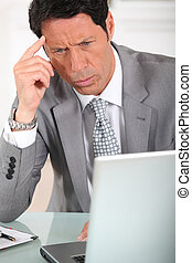 Businessman with a puzzled expression looking at a computer...