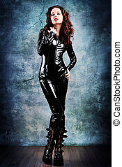 overall - Fashion shot of a woman in black glossy overall...