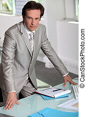 Man in a silver-grey suit purposefully standing by his desk