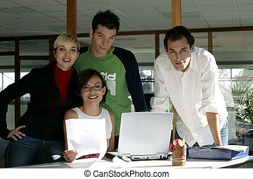 Young creative team standing with a laptop computer