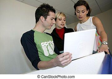 Creative team working around a laptop