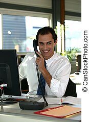 businessman at his desk talking on the phone