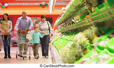 Shopping family - Family of four pushing cart full of...