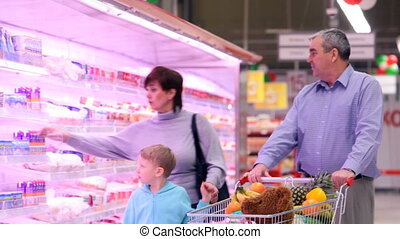 Family in supermarket - Family of three pushing trolley full...
