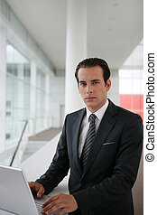 Serious businessman using a laptop computer