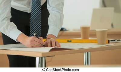 Drawing a scheme - Serious young man drawing a scheme or a...