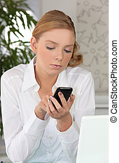 Young fair-haired woman sending text message