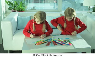 Twins drawing - Two twin girls drawing at home with colorful...