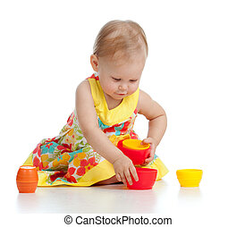 Cute little child is playing with toys while sitting on floor, isolated over white