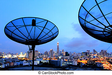 black antenna communication satellite dish over sunset sky...