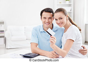 Finance - A young couple with a credit card at home