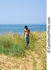 Muscular male model on the beach walking in a corn field