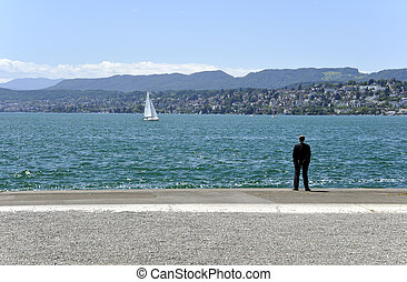 businessman contemplating a lake - businessman contemplating...
