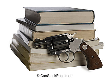 Textbooks and pistol - A 38 caliber pistol stands in front...