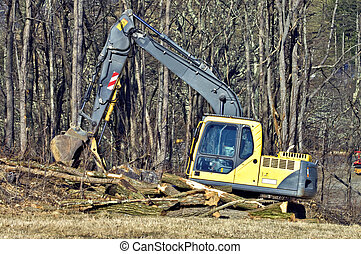 Heavy Equipment and Logs - A large bucket machine at a...