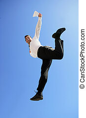 Businessman jumping against a blue sky