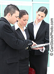 Three young executives standing outside a workplace