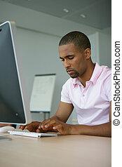 Man typing at computer