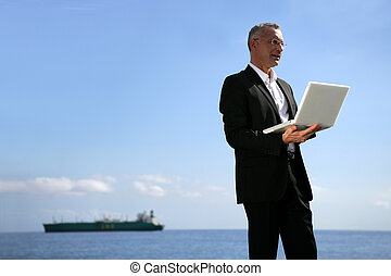 Businessman using his laptop by the water's edge