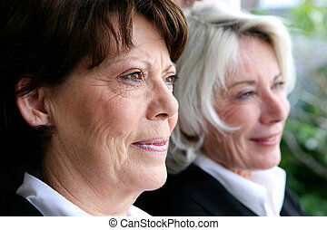 two mature businesswomen posing together
