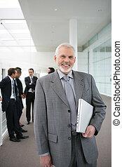 Senior businessman standing in a corridor