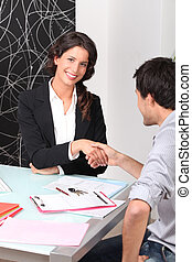 Two people shaking hands over a contract