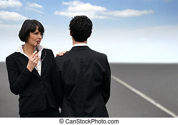 Conceptual shot of a business couple standing facing...