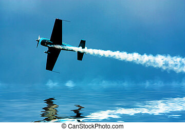 Stunt plane flying close to water with smoke trails