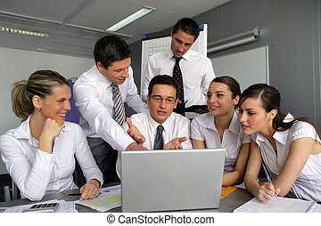 Business team gathered around laptop