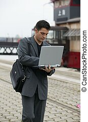 Businessman using his laptop outdoors