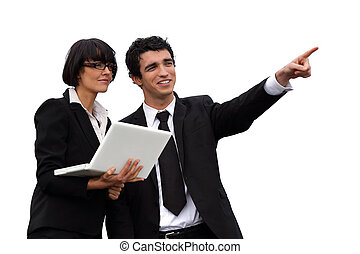 Business people with a laptop pointing into the distance