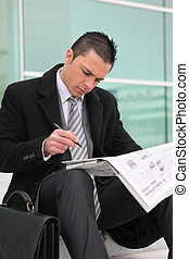 a young businessman looking newspaper