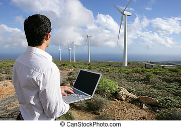 Man with laptop in wind farm