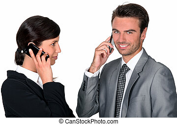 Two businesspeople making simultaneous calls
