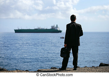 Businessman staring at a tanker out at sea